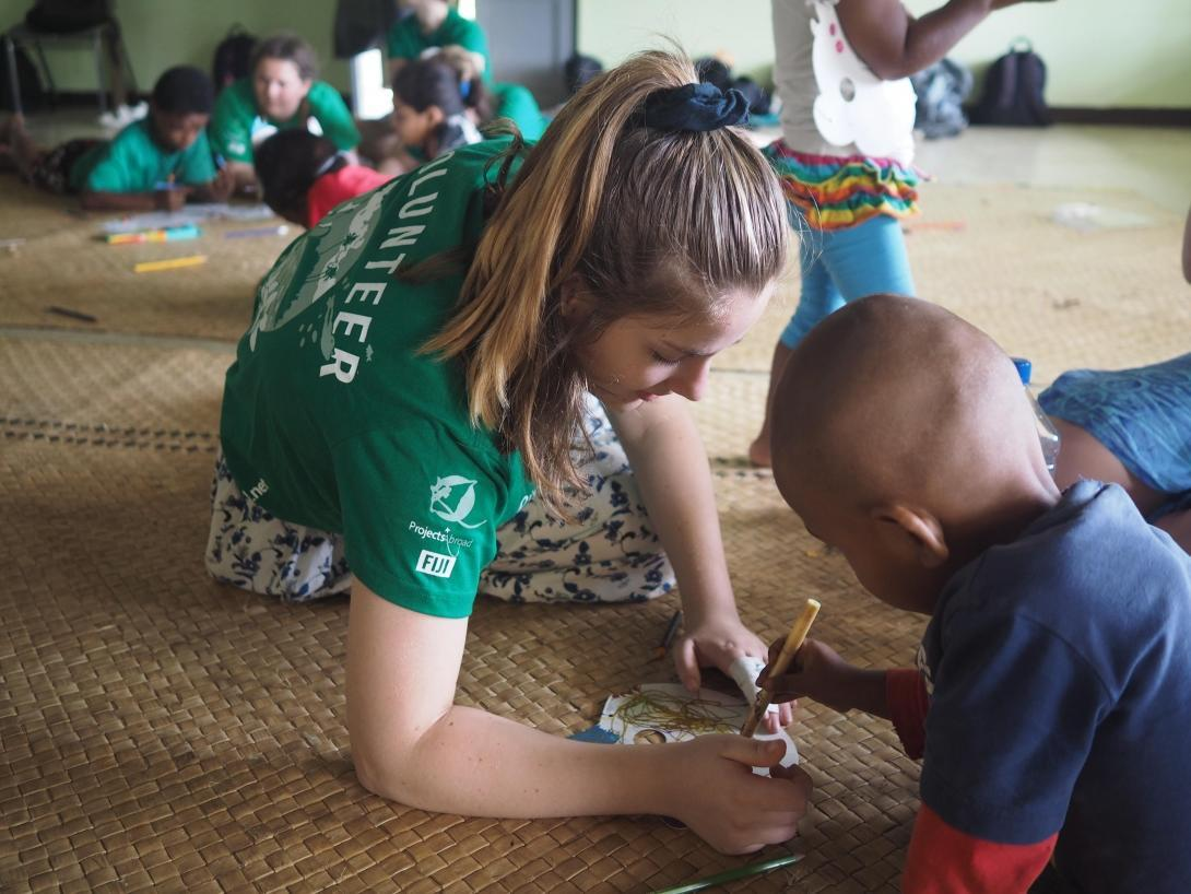 Projects Abroad volunteer with children in Fiji sits on the floor of a special needs day school to help a child to draw during her Childcare Project.